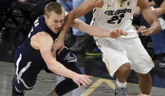 J.P. Macura, left, of Xavier, and Derrick White, of Colorado, chase down a loose ball during an NCAA college basketball game in Boulder, Colo., Wednesday, Dec. 7, 2016. (Cliff Grassmick/Daily Camera via AP)