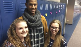 ADVANCE FOR USE SUNDAY, DEC. 11, 2016 AND THEREAFTER - In this Nov. 15,  2016 photo, students at Warren Township High School's junior-senior Almond Road campus in Gurnee, Ill., from left, Kathryn Haynes, Jaylen Davis and Amanda Middleton were among those who wrote positive messages on sticky notes and posted them on all 2,500 lockers in response to racist graffiti that was found on bathroom stalls at Warren's two campuses the previous week. (Bob Susnjara/Daily Herald, via AP)