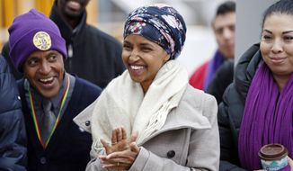 In this Tuesday, Nov. 29, 2016, file photo, Ilhan Omar, center, applauds during a rally at the Minneapolis-St. Paul International Airport in Minneapolis. Omar, the nation's first elected Somali-American lawmaker, says she was harassed by a taxicab driver in Washington, D.C. this week. (AP Photo/Jim Mone, File)