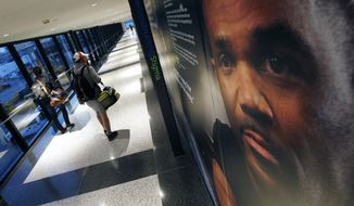 Passengers walk past an art exhibit at Logan International Airport in Boston, Thursday, Dec. 8, 2016. The exhibit consists of larger-than-life posters of nearly three dozen people _ some ordinary, some famous _ who have struggled with mental illness. A portrait of Run-D.M.C founder Darryl McDaniels is at right. (AP Photo/Michael Dwyer)