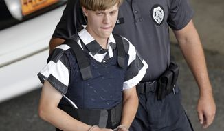 FILE - In this June 18, 2015 file photo, Charleston, S.C., shooting suspect Dylann Storm Roof is escorted from the Cleveland County Courthouse in Shelby, N.C. Prosecutors who wanted to show that Roof was a cruel, angry racist simply used his own words at his death penalty trial on charges he killed nine black people in June 2015 at a Charleston church. Roof's two-hour videotaped confession less than a day after the shooting and a handwritten journal found in his car when he was arrested were introduced into evidence Friday, Dec. 9, 2016. (AP Photo/Chuck Burton, File)