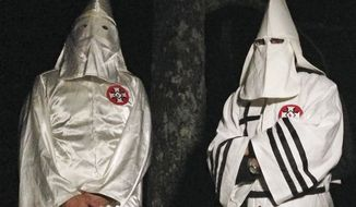In this Friday, Dec. 2, 2016, photo, two masked Ku Klux Klansmen stand on a muddy dirt road during an interview near Pelham, N.C. (AP Photo/Jay Reeves) ** FILE **