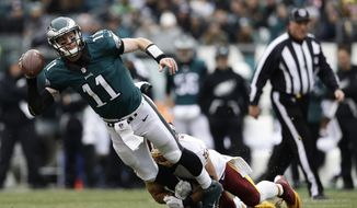 Philadelphia Eagles' Carson Wentz, left, is tackled as he passes by Washington Redskins' Ryan Kerrigan during the first half of an NFL football game against the Washington Redskins, Sunday, Dec. 11, 2016, in Philadelphia. (AP Photo/Matt Rourke)
