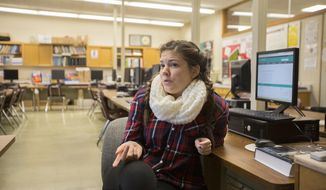 In a Dec 2, 2016 photo, Danielle Wendricks, president the Key Club, monitors the food pantry at La Follete High School, in Madison, Wis. The group is giving back to its own student body through an on-campus food pantry. (Saiyna Bashir /The Capital Times via AP)