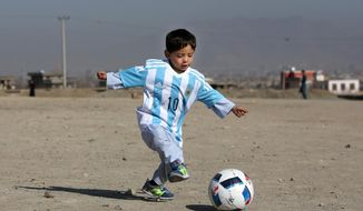 FILE - A Friday, Feb. 26, 2016 photo from files of Murtaza Ahmadi, a five-year-old Afghan Lionel Messi fan playing with a soccer ball during a photo opportunity as he wears a shirt signed by Messi, in Kabul, Afghanistan. Murtaza made a special trip from Afghanistan to Qatar, where Messi was with his Barcelona teammates to play a friendly match against Al Ahli on Tuesday, Dec. 13, 2016. In a meeting arranged by the organizing committee of the 2022 World Cup in Qatar, Messi held hands with Murtaza at the team hotel before picking up the boy and posing for photographs. Murtaza was wearing a Barcelona jersey.  (AP Photo/Rahmat Gul, File)
