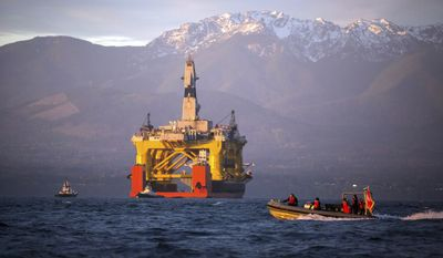 In this April 17, 2015, file photo, with the Olympic Mountains in the background, a small boat crosses in front of the Transocean Polar Pioneer, a semi-submersible drilling unit that Royal Dutch Shell leases from Transocean Ltd., as it arrives in Port Angeles, Wash., enroute to its eventual Arctic destination. (Daniella Beccaria/seattlepi.com via AP, File)