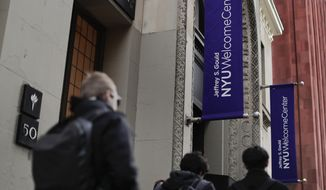 Students walk along West 4th Street in front of the Jeffrey S. Gould learning center, Wednesday, Dec. 14, 2016, in New York. New York University has introduced a program to help students save money by putting them up in elderly people's spare bedrooms. The plan has gotten serious consideration from some students straining under the institution's $66,000 annual tuition. (AP Photo/Julie Jacobson)