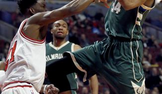Milwaukee Bucks forward Giannis Antetokounmpo, right, is fouled by Chicago Bulls guard/forward Jimmy Butler while driving to the basket during the first half of an NBA basketball game Friday, Dec. 16, 2016, in Chicago. (AP Photo/Nam Y. Huh)