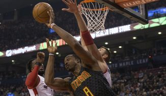 Atlanta Hawks center Dwight Howard, center, passes under the basket despite pressure from Toronto Raptors center Jonas Valanciunas, left, and DeMarre Carroll during first-half NBA basketball action in Toronto, Friday, Dec. 16, 2016. (Chris Young/The Canadian Press via AP)