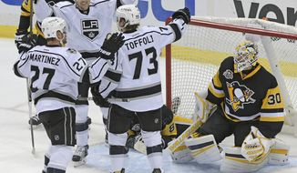Los Angeles Kings defenseman Alec Martinez (27), left wing Tanner Pearson (70), and center Tyler Toffoli (73) celebrate the winning goal next to Pittsburgh Penguins goalie Matt Murray (30) during the overtime period of an NHL hockey game on Friday, Dec. 16, 2016, in Pittsburgh. (AP Photo/Fred Vuich)