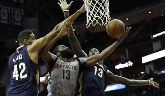 Houston Rockets' James Harden (13) is fouled as he goes up for a shot between New Orleans Pelicans' Alexis Ajinca (42) and Cheick Diallo (13) during the second half of an NBA basketball game Friday, Dec. 16, 2016, in Houston. The Rockets won 122-100. (AP Photo/David J. Phillip)