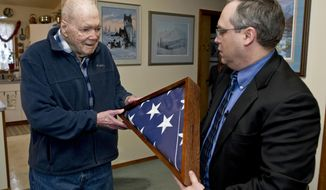 ADVANCE FOR WEEKEND EDITIONS USE, DEC. 17-18, 2016, AND THEREAFTER. FILE - In this Thursday, Dec. 8, 2016, photo, Lt. Col. Pat Carothers, left, receives a U.S. flag from Supervisory Deputy U.S. Marshal John Olson in honor of his son, U.S. Marshal Deputy Commander Patrick Carothers, 53, at his home in Juneau. Deputy Commander Carothers was gunned down Nov. 18 during the arrest of 25-year-old Dontrell Carter while in Georgia. Lt. Col. Carothers, 90, a veteran of WWII, Korea and Vietnam wars, was unable to attend the funeral for health issues. (Michael Penn/The Juneau Empire via AP)