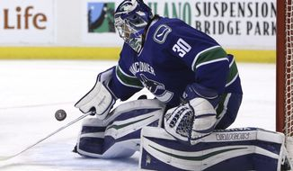 Vancouver Canucks' goaltender Ryan Miller (30) makes a save during the first period of an NHL hockey game against the Tampa Bay Lightning, Friday, Dec. 16, 2016 in Vancouver, British Columbia.  (Ben Nelms/The Canadian Press via AP)
