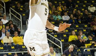 Michigan forward D.J. Wilson (5) dunks over Maryland-Eastern Shore forward Bakari Copeland (21) during the first half of an NCAA college basketball game at Crisler Center in Ann Arbor, Mich., Saturday, Dec. 17, 2016. (AP Photo/Tony Ding)