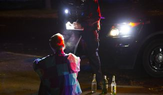 In this Friday, Nov. 19, 2016 photo, a Eugene police officer issue a citation to a student for an open container violation during a Friday night party patrol of the neighborhood near the University of Oregon in Eugene, Ore. (Chris Pietsch  /The Register-Guard via AP)