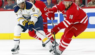 Carolina Hurricanes' Jay McClement (18) moves the puck around Buffalo Sabres' Evander Kane (9) during the first period of an NHL hockey game, Saturday, Dec. 17, 2016, in Raleigh, N.C. (AP Photo/Karl B DeBlaker)