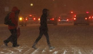As traffic backs up in the background, pedestrians struggle to cross Speer Boulevard at a stop light as a winter storm swept over the metropolitan area late Friday, Dec. 16, 2016, in Denver. Forecasters predict that the fast-moving storm will move on to the eastern plains but subzero temperatures will chill the region Saturday. (AP Photo/David Zalubowski)