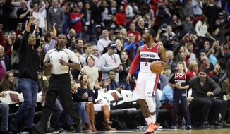 Washington Wizards guard John Wall gets the fans excited in the final seconds of a 117-110 victory over the Los Angeles Clippers on Sunday. (Associated Press)