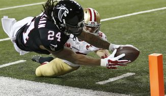 Atlanta Falcons running back Devonta Freeman (24) makes the reach near the goal line as =s40 defends during the first half of an NFL football game, Sunday, Dec. 18, 2016, in Atlanta. (AP Photo/John Bazemore)