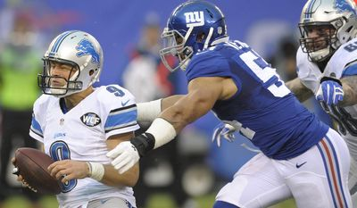 Detroit Lions quarterback Matthew Stafford (9) spins to avoid a sack by New York Giants' Olivier Vernon (54) during the first half of an NFL football game Sunday, Dec. 18, 2016, in East Rutherford, N.J. (AP Photo/Bill Kostroun)