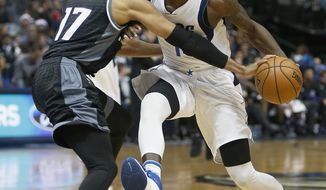 Dallas Mavericks forward Dorian Finney-Smith, right, is fouled by Sacramento Kings guard Garrett Temple (17) while driving to the basket in the first half of an NBA basketball game on Saturday, Dec. 18, 2016 in Dallas . (AP Photo/Brad Loper)
