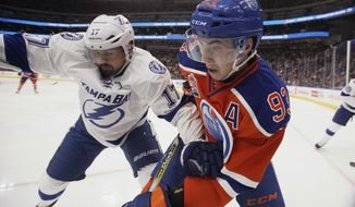 Tampa Bay Lightning's Alex Killorn (17) and Edmonton Oilers' Ryan Nugent-Hopkins (93) battle in the corner during the second period of an NHL hockey game in Edmonton, Alberta, Saturday, Dec. 17, 2016. (Jason Franson/The Canadian Press via AP)
