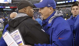 New York Giants head coach Ben McAdoo, right, and Detroit Lions head coach Jim Caldwell, left, meet after an NFL football game Sunday, Dec. 18, 2016, in East Rutherford, N.J. The Giants won 17-6. (AP Photo/Seth Wenig)