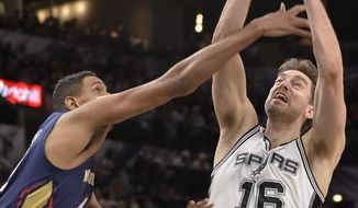 San Antonio Spurs center Pau Gasol (16), of Spain, grabs for a rebound against New Orleans Pelicans center Alexis Ajinca, of France, during the first half of an NBA basketball game, Sunday, Dec. 18, 2016, in San Antonio. (AP Photo/Darren Abate)