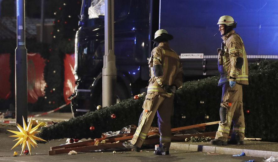 Firefighters look at a toppled Christmas tree after a truck ran into a crowded Christmas market in Berlin, Germany, on Monday. (Associated Press)