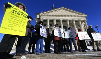 Protesters against President-elect Donald Trump hold signs outside the Kansas Statehouse in Topeka, Kan., Monday, Dec. 19, 2016. Six electors of the Electoral College will cast their votes inside the Senate chambers. (AP Photo/Orlin Wagner)