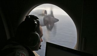 In this March 22, 2014, file photo, flight officer Rayan Gharazeddine scans the water in the southern Indian Ocean off Australia from a Royal Australian Air Force AP-3C Orion during a search for the missing Malaysia Airlines Flight MH370. A team of international investigators hunting for missing Malaysia Airlines Flight 370 said Tuesday, Dec. 20, 2016, it has concluded the plane is unlikely to be found in a stretch of the Indian Ocean search crews have been combing for two years, and may instead have crashed in an area farther to the north. (AP Photo/Rob Griffith, File)