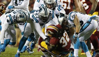 Washington Redskins running back Rob Kelley (32) is overwhelmed by the Carolina Panthers defense during the second half of an NFL football game in Landover, Md., Monday, Dec. 19, 2016. (AP Photo/Alex Brandon)