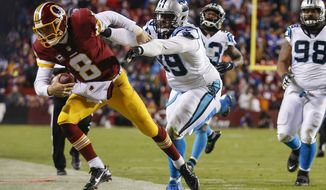 Washington Redskins quarterback Kirk Cousins (8) is forced out of bounds by Carolina Panthers defensive tackle Kawann Short (99) during the second half of an NFL football game in Landover, Md., Monday, Dec. 19, 2016. (AP Photo/Alex Brandon)