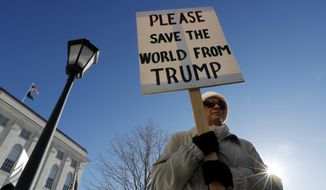 Davina Foti of Exeter, N.H., attends a protest against President-elect Donald Trump Monday, Dec. 19, 2016, at the State House in Augusta, Maine. Maine's electoral college voters split their vote with 3 ballots for Hillary Clinton and one for Trump. (AP Photo/Robert F. Bukaty)