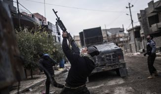 In this Sunday, Dec. 18, 2016 photo, a aember of the Iraqi Special Forces shoots his machine gun against an Islamic State militant drone n the al-Barid district in Mosul, Iraq. In a part of Mosul that had been reclaimed from the Islamic State group (IS) days ago, Iraqi special forces were attacked on Sunday by drones operated by IS fighters inside the city.(AP Photo/Manu Brabo)