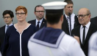 French Defense Minister Jean-Yves Le Drian, right, and Australian Defense Minister Marise Payne listen to national anthems on the Australian Navy ship HMAS Adelaide in Sydney, Monday, Dec. 19, 2016. The Australian and French defense ministers say they are giving top priority to concealing design details of a new Australian submarine after data was leaked from French shipbuilder DCNS about a submarine built for India. (Jason Reed/Pool Photo via AP)