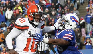 Cleveland Browns quarterback Robert Griffin III (10) stiff arms Buffalo Bills outside linebacker Jerry Hughes (55) during the first half of an NFL football game, Sunday, Dec. 18, 2016, in Orchard Park, N.Y. (AP Photo/Jeffrey T. Barnes)