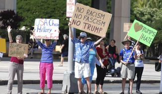 Protesters rally outside the Hawaii State Capitol on Monday Dec. 19,2016, in Honolulu. They were protesting the President-elect Donald Trump and the Electoral College. (AP Photo/Cathy Bussewitz)