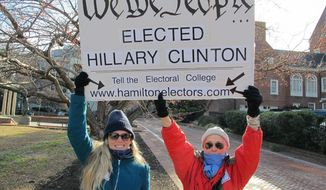 Cheryl Kreiser, right, and Krista Keyes demonstrate in front of the Maryland State House in Annapolis, Md., Monday, Dec. 19, 2016, hours before Maryland's 10 electors were scheduled to cast the state's electoral votes for Hillary Clinton. (AP Photo/Brian Witte)