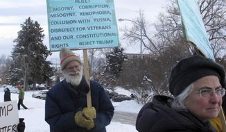Gary and Dona Aitken protest President-elect Donald Trump outside the Capitol in Helena, Mont., before the electoral college votes Monday, Dec. 19, 2016. (AP Photo/Matt Volz)