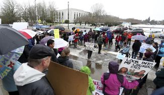 Protestors encourage electors to vote against Donald Trump and call for general electoral college reform outside the Oregon State Capitol in Salem, Ore., on Monday, Dec. 19, 2016. (Anna Reed /Statesman-Journal via AP)