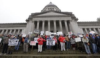 Protesters chant on the steps of the statehouse against Electoral College voting, Monday, Dec. 19, 2016, in Olympia, Wash. Members of Washington state's Electoral College met at noon Monday in the Capitol to complete the constitutional formality. (AP Photo/Elaine Thompson)