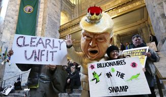 Jo Walter, of Bremerton, Wash., wears a large Donald Trump head mock-up as she protests Electoral College voting Monday, Dec. 19, 2016, in Olympia, Wash. Members of Washington state's Electoral College met at noon Monday in the Capitol to complete the constitutional formality. (AP Photo/Elaine Thompson)