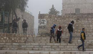 Jordanian security forces guard an entrance, left, as boys walk past in the morning mist in front of Karak Castle in the central town of Karak, about 140 kilometers (87 miles) south of the capital Amman, in Jordan Monday, Dec. 19, 2016. Gunmen assaulted Jordanian police in a series of attacks Sunday, including at the Karak Crusader castle popular with tourists, killing seven officers, two local civilians and a woman visiting from Canada, officials said. (AP Photo/Ben Curtis)