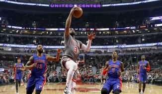 Chicago Bulls' Dwyane Wade (3) scores past Detroit Pistons' Marcus Morris (13) and Kentavious Caldwell-Pope during the first half of an NBA basketball game Monday, Dec. 19, 2016, in Chicago. (AP Photo/Charles Rex Arbogast)