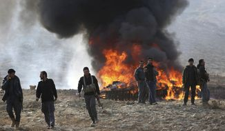 Afghan security personnel watch as flames and smoke rise after opium and narcotics are burned in a ceremony in Kabul, Afghanistan, Tuesday, Dec. 20, 2016. Afghan officials burned down a total of 98 tons of opium, heroin, hashish and alcoholic drinks at the outskirts of Kabul, the capital. (AP Photos/Massoud Hossaini)
