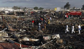 Firefighters and rescue workers walk through the scorched ground of Mexico's best-known fireworks market after an explosion explosion ripped through it Tuesday in Tultepec, Mexico. (Associated Press)
