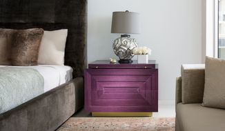 This photo provided by Brown Davis Interiors shows a rich purple console inside a penthouse apartment bedroom. Designed by Brown Davis and crafted by Keith Fritz Fine Furniture, the Barry console is part of a collection of richly-hued furniture that takes a cue from Art Deco and makes it thoroughly modern. (Moris Moreno/Brown Davis Interiors via AP)