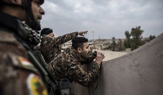 Iraqi members of the Special Forces scan the area held by Islamic state militants from a roof in Mishraq district in Mosul, Iraq, Tuesday, Dec. 20, 2016. Advancing into Mosul has become a painful slog for Iraqi forces. Islamic State group militants have fortified each neighborhood, unlike past battles where they concentrated their defenses in one part of the city. (AP Photo/Manu Brabo) ** FILE **