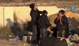 In this still image taken from video released by Baladi News, a Syrian opposition-affiliated media outlet, on Tuesday, Dec. 20, 2016, Aleppo kids eat after arriving to the city's countryside as part of an evacuation process that commenced last week. The International Committee for the Red Cross said it has overseen the evacuation of 25,000 people from east Aleppo since rebels effectively surrendered the area to the Syrian government. (Baladi News via AP)